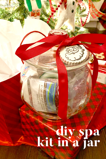 glass jar filled with all kinds of spa items, tied with a red ribbon and a santa ornament