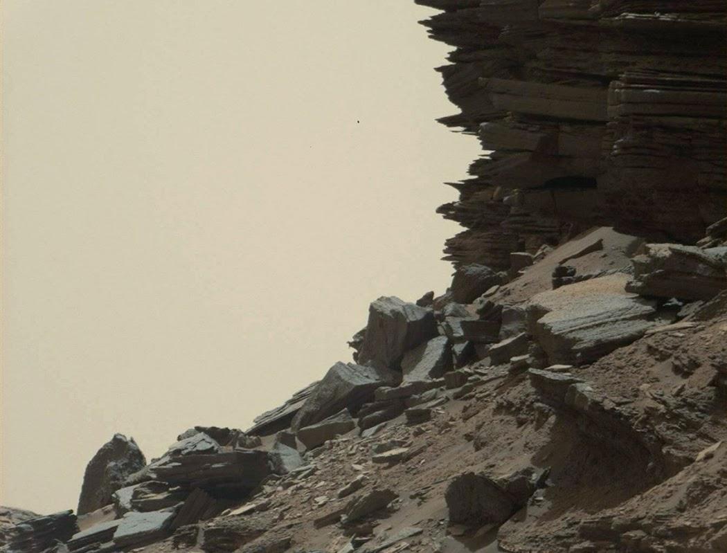 Hình này này được chụp từ Mastcam cho thấy một sườn đồi với các tầng đá ở khu vực Đồi Murray, gần chân núi Sharp. Ngọn đồi này không thoải dài như bình thường nhưng mang dấu vết của sự xói mòn của sa thạch cổ khi những cơn gió mạnh thổi qua vùng này. Tàu Curiosity đã đến đây để thăm dò ở khoảng cách gần nhất vào nửa đầu năm 2016. Để đến được đây, con tàu phải đi qua khu vực Cao nguyên Naukluft thuộc vùng Murray này. Gió làm sa thạch xếp lớp trong hình này cũng giống như cách nó tạo hình dạng cho những đồi cát. Hình ảnh được chụp vào ngày 8 tháng 9 năm 2016, tức nhằm sol 1454. Hình ảnh: JPL-Caltech/MSSS/NASA.
