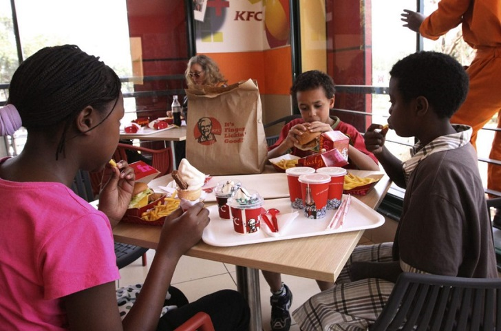 Young children enjoy lunch at a Kentucky Fried Chicken restaurant