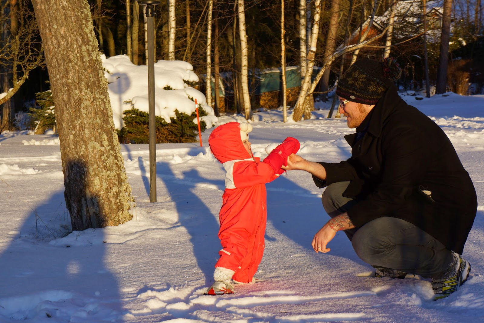 toddler playing with daddy in snow