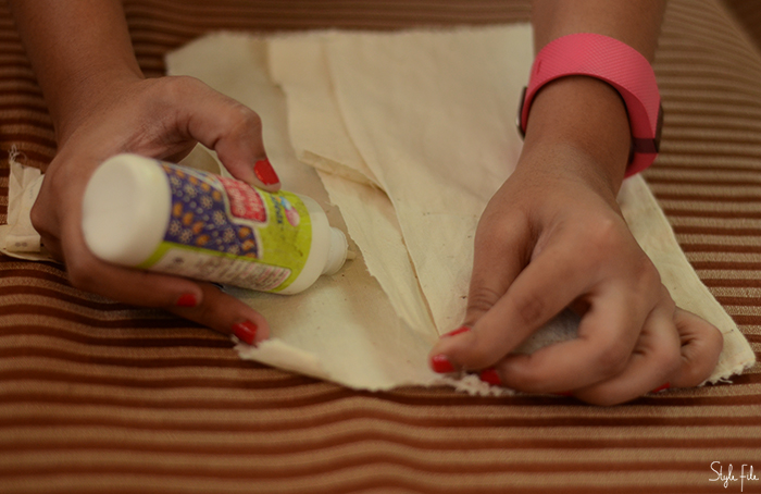 An image of canvas cloth being glued by a woman with orange nails and a pink FitBit for a do-it-yourself mini crossbody sling bag project on Style File