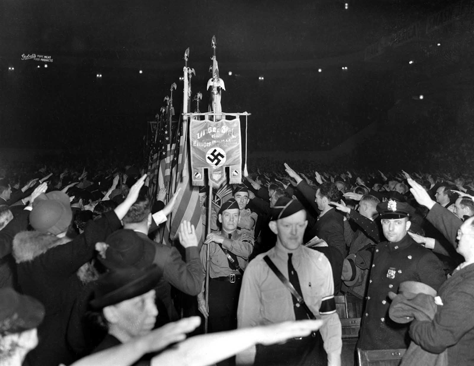 The crowd responds with a Nazi salute as uniformed members of a German-American Bund color guard march at a gathering in New York's Madison Square Garden, on February 20, 1939.