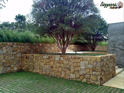 Detalhe dos muros de pedra com patamares e as mudas de jaboticaba plantadas e o piso com concre-grama.