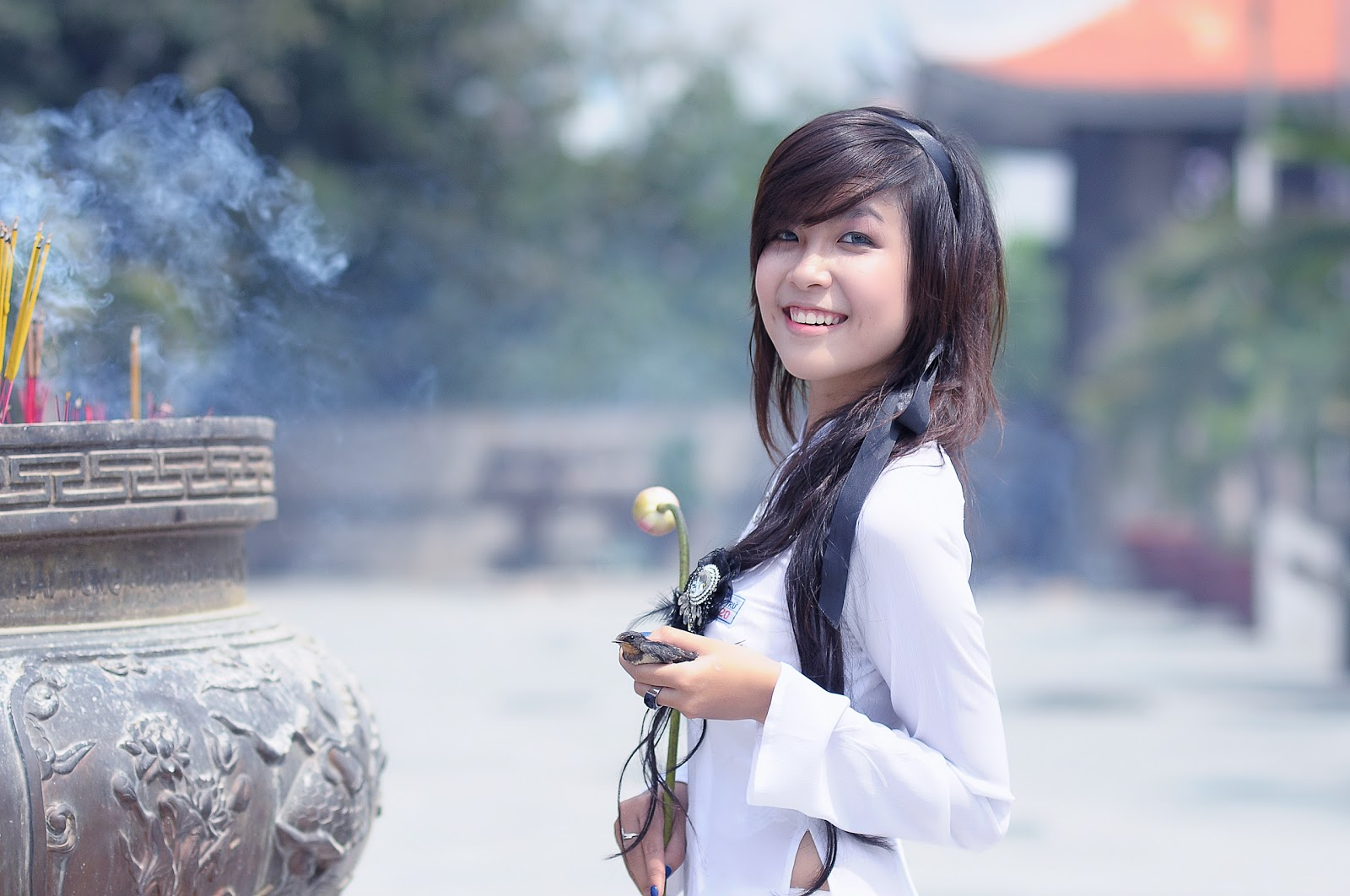 白い服を着て立っている笑顔の少女