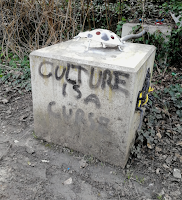 an image of a beetle sculpture sitting atop a square pedestal, with the text Culture is a curse sprayed on the pedestal
