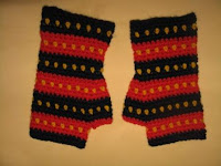 A pair of fingerless mitts in Adelaide Crows' colours. They have horizontal stripes, alternating navy and red. Each stripe has a row of yellow dots centred horizontally on the stripe. For example, starting at the cuff the colours are solid navy, yellow dots against the navy, solid navy; solid red, yellow dots against the red, solid red; and so forth ending with a row of solid navy at the fingers.