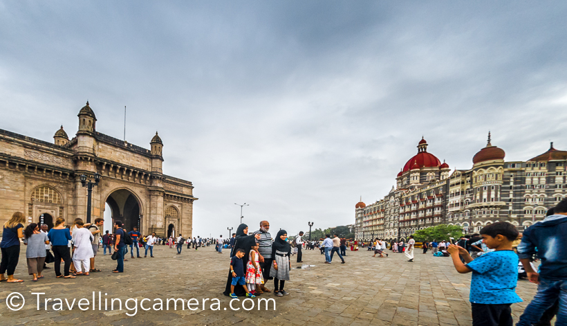 Few weeks back I was in Mumbai for 2 days and had great company to explore this beautiful town in monsoons. This Photo Journey shares about Gateway of India, which is one of the most visited places in Mumbai and things to do around it. Gateway of India is surrounded by some of the best architectures in Mumbai and few popular restaurants & cafes.And if you are visiting Gateway of India, it makes sense to also know about other interesting things to do around it. So this post also talks about main things to do around Gateway of India and the famous Taj Mahal Palace Hotel.Gateway of India is located on waterfront and was built in 20th century. This beautiful architecture is in south Delhi. I was staying near Airport and it took 1.5 hrs to reach Gateway of India from our hotel. This is most visited place in Mumbai city.If you like knowing or photographing architecture, there are some beautiful buildings around Gateway of India. I highly recommend to walk around Gateway of India on foot and explore some of the beautiful buildings around the famous Taj Mahal Palace hotel.There is also a street behind Taj Mahal Palace hotel for people who love to do some shopping. There are lot of kiosks selling artificial jewelry. I didn't do any shopping here, but it seemed that lot of negotiation happens in these street, which is not very surprising.There are lot of beautiful buildings all around. It was my first visit to Mumbai and the city lot of old structures surrounded by high-rise apartments.Here is a photograph of the famous Leopold Cafe & Bar . I am sure you would have heard of this name. If it's getting a little difficult, let me help in reminding that cafe was impacted by terror attack in 2008. I loved these windows. This whole street behind famous Taj Mahala Palace Hotel has beautiful windows. I wish I had more time to observe them in a better way and capture through my Travellingcamera.I know traffic of Mumbai is talked about a lot, but I must say that traffic police does a great job. And most of the drivers are quite disciplined. Lack of these 2 would certainly convert the whole thing into chaos. We drove from Sahar to Colaba in a cab at around 3pm and it took us 1.5 hrs. During evening it may take somewhere around 2.5 hrs to 3 hrs (told by our hotel staff).Above is photograph of famous Taj Mahal Palace Hotel and you can see horse carts in front of it. Tourists can have a tour around this place in these horse carts.When I pointed my camera towards this building, this couple was wondering what am I clicking here. Notice the smile on the face of this boy and girl is looking back to figure out my subject :)Group of photographer friends around Gateway of India. It was time to relax a bit. These guys click photographs of tourists around Gateway of India and hand-over the printouts in few minutes. It's certainly a very tiring job to be on feet all the day, creating beautiful memories for tourists and try best to deliver good quality.