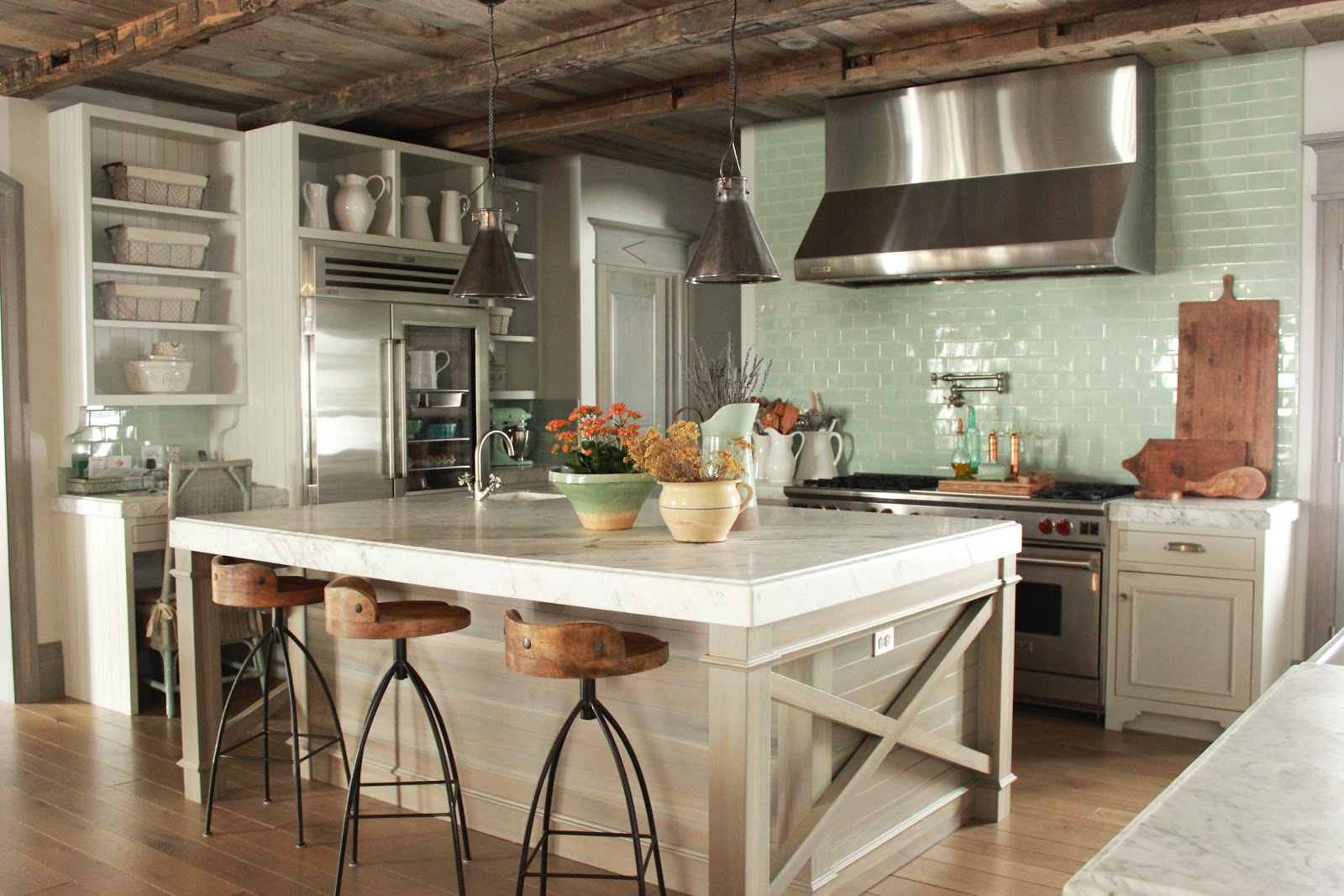 Magnificent Gustavian French kitchen in stone cottage with rustic interiors, reclaimed wood ceilings, blue-grey, green, and collected European antiques. Designed by Desiree Ashworth. Find ideas for grey, blue, and green paint colors.