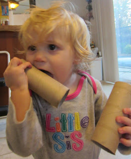 toddler chewing on toilet paper tubes