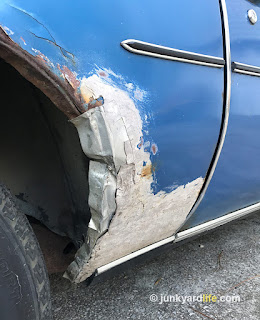 Poorly repaired quarter panel features aluminum can patch and bondo.