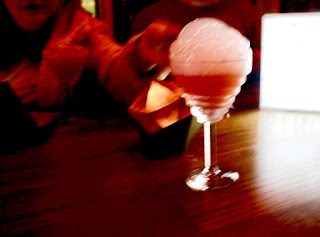 A long stemmed martini glass filled with pink liquid and topped with white bubbles on a large rectangular wooden table on a dark background