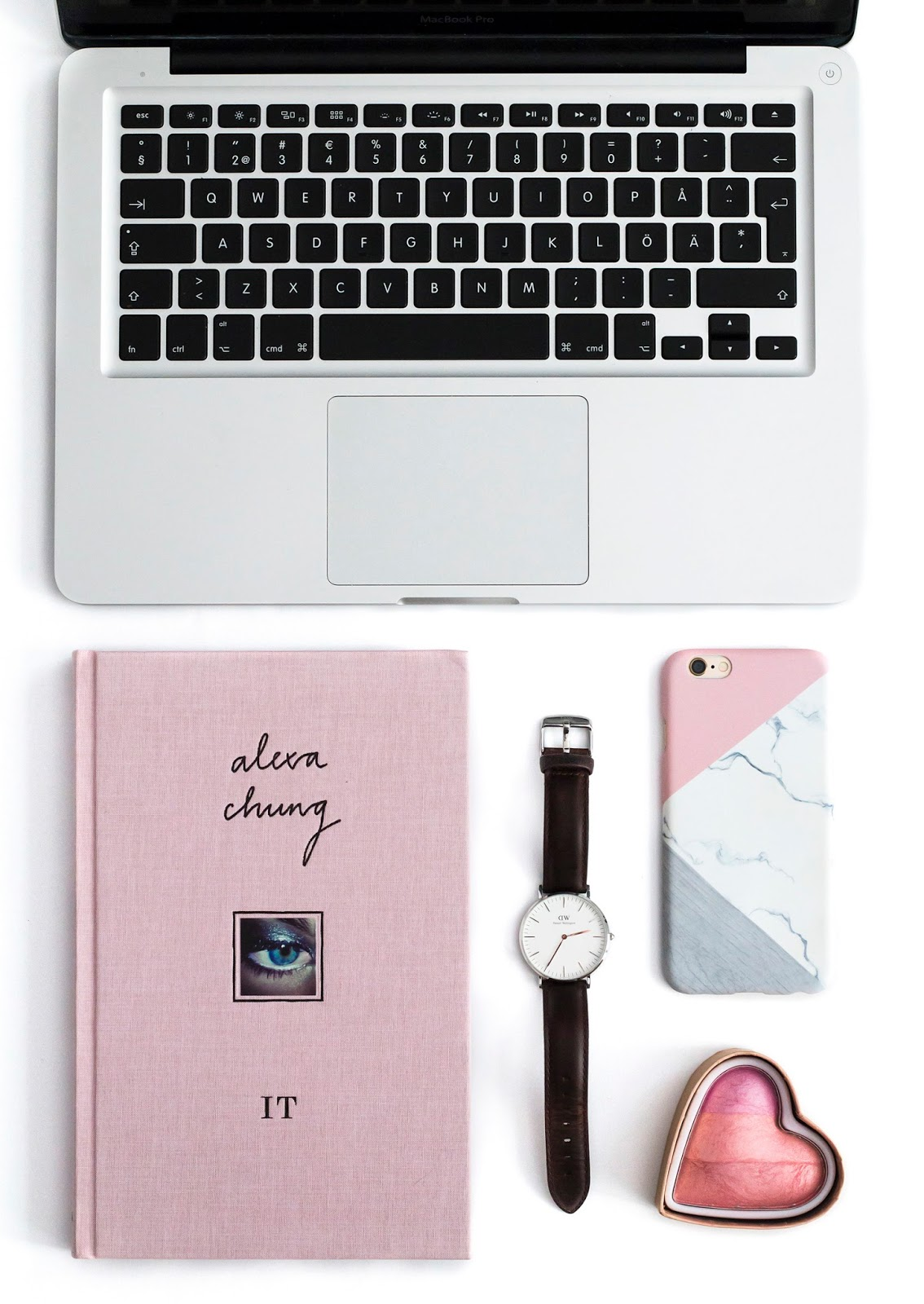 Lifestyle and beauty flatlay. Macbook, pink book, heart blush, Daniel Wellington.