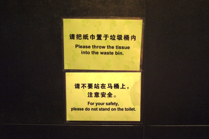signs saying Please throw the tissue into the waste bin and For your safety do not stand on the toilet