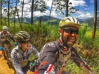 Foto de apoio a projeto com deficiente visual. Na imagem, deficiente visual pedalando com guia em bike tandem.