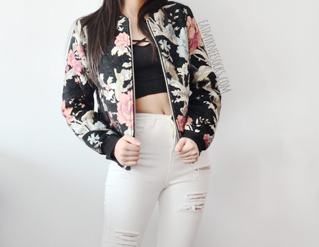 A grunge-chic outfit featuring Make Me Chic's embroidered floral bomber jacket and white high-waisted distressed ripped skinny jeans, paired with a Brandy Melville style cropped tank top and quilted leather high-heel boots.