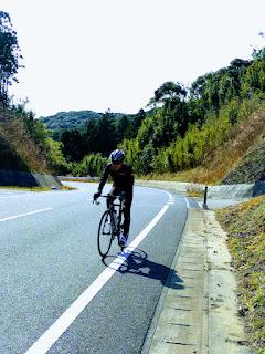 坂道で必死で自転車を漕いでいる旦那