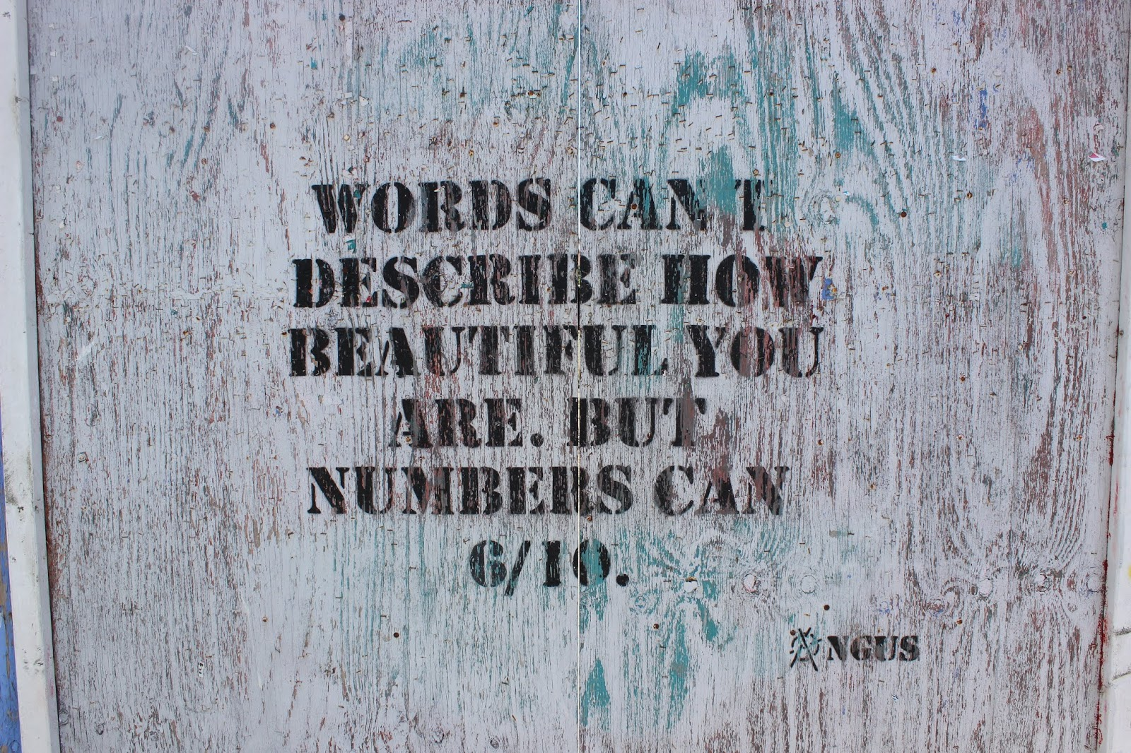 Wall graffiti stating 'Words can't describe how beautiful you are, but numbers can. 6/10'.