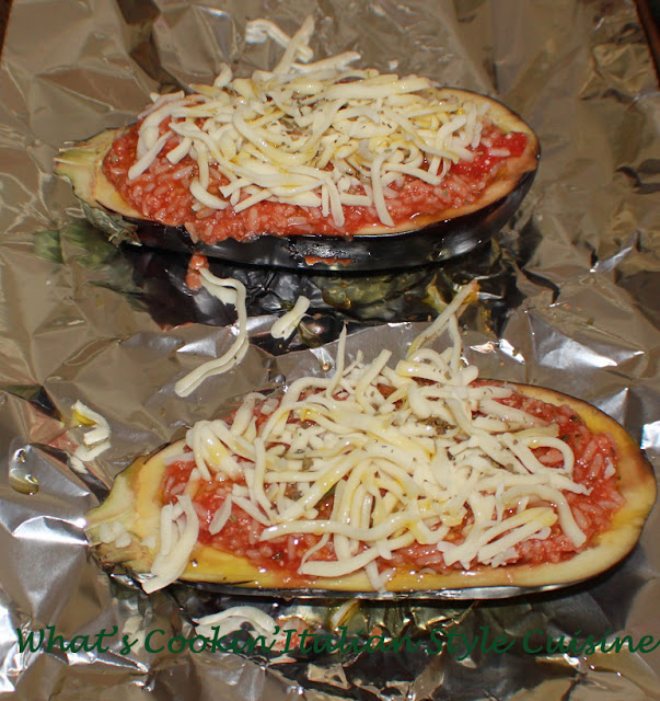 these are stuffed eggplant boats on foil ready to be cooked on a roasting sheet