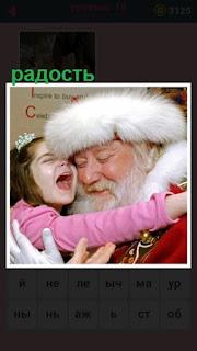 ребенок в объятиях деда мороза проявляя радость на лице