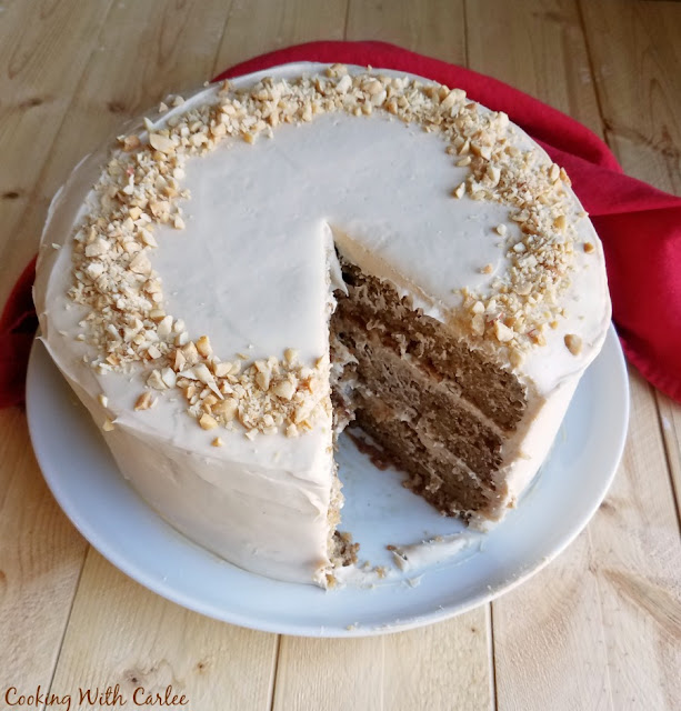 layered applesauce cake with soft and creamy caramel cream cheese frosting and a big slice missing showing the layers