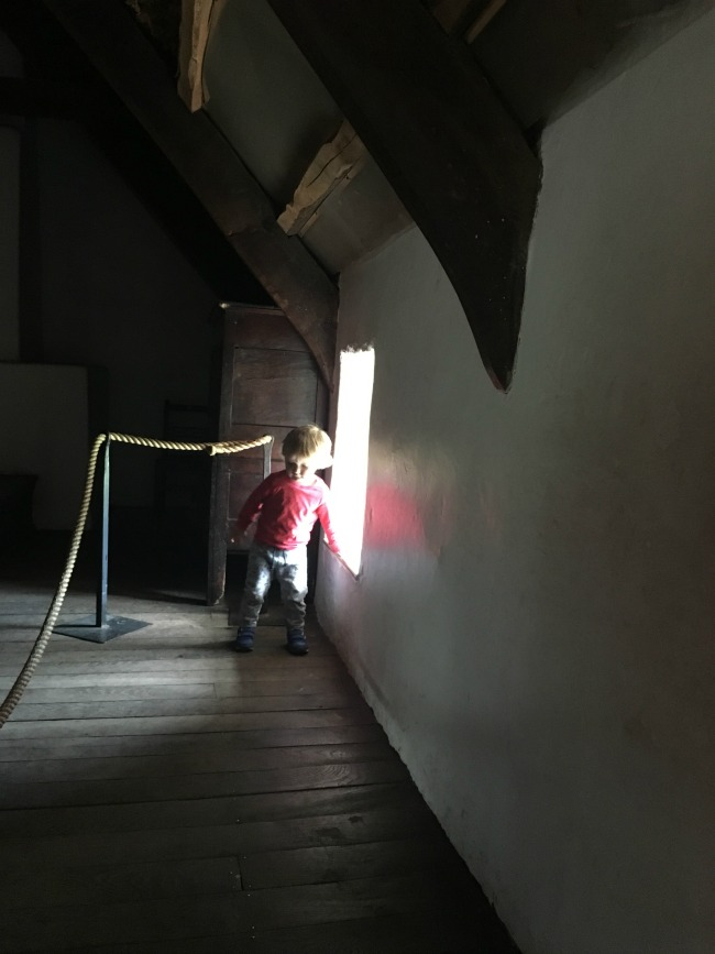toddler-walking-away-from-window-sill-inside-cottage-at-St-Fagans