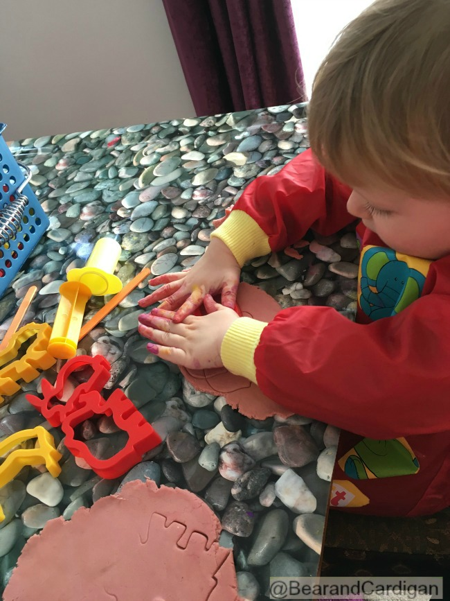 toddler with paint on hands using cutters on play dough