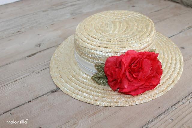 Sombrero tipo canotier de copa baja con cinta en crudo y flores rojas con hojas verdes