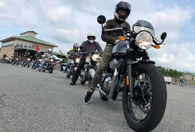 Line of motorcycle riders prepares to head out onto race track.