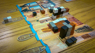 The five main play boards, each with a variety of blocks, in white, black, brown, and grey, stacked on them in different ways. The Market Board is the exception; it has no blocks, but does have some market cards on it. The boat tokens are docked with four of the five boards by having their prow placed in the notch on the left side of the board. All the blocks that were on these boats have been moved to the play boards, except a white one and a grey one on the second boat which haven't yet been transferred.