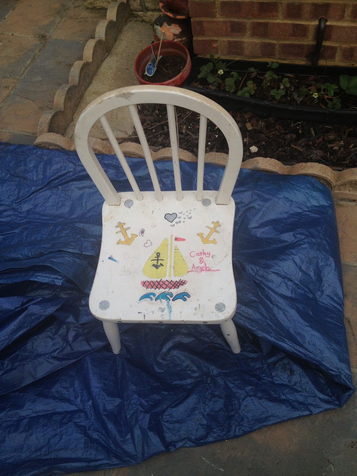 A white chair with doodles on the seat.