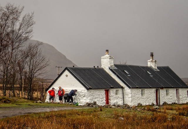Photo of walkers sheltering from the rain behind Blackrock Cottage