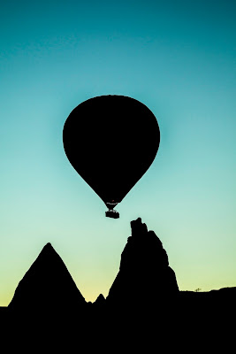 silhouette of hot air balloon over two pointy mountains