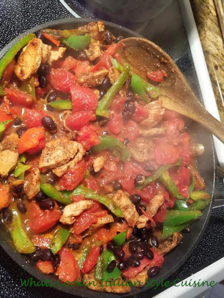 beans and peppers with chickens in a fry pan sauteed