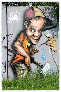 Sapkás alak festőhengerrel a kezében graffiti Szegeden a körtöltésen