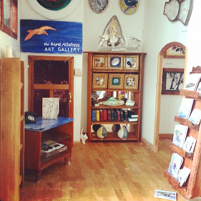 Miniature art gallery, with various items displayed for sale and a counter in one corner. On the wall is a sign saying 'the Royal Albatross art gallery'.