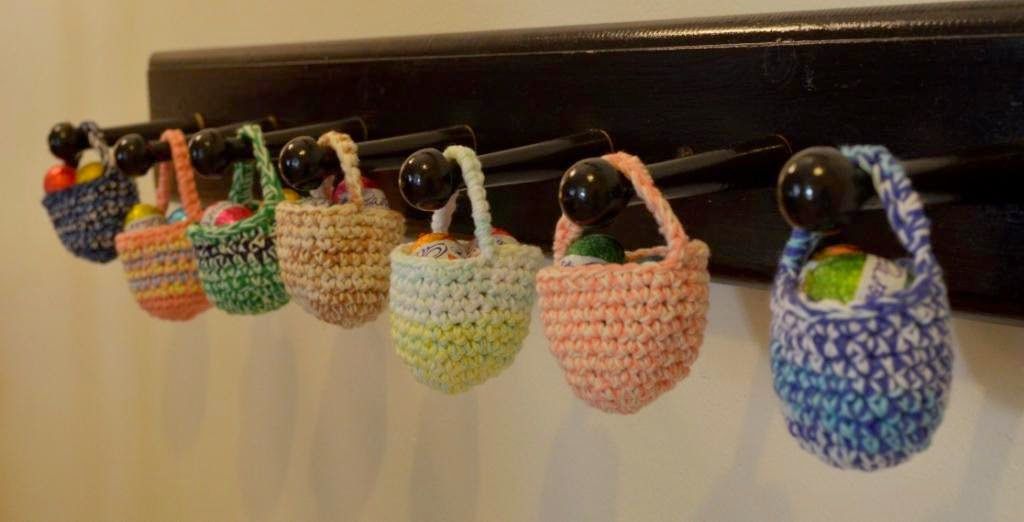 A row of seven wooden wall pegs (painted black), each peg has a mini easter basket hanging on it. Each mini basket is crocheted in a unique colour and contains mini eggs.