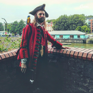 Blood, Booze and Buccaneers, Bristol, Theatre tour: a pirate leans against a wall smiling. His parrot is on his shoulder.