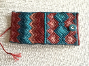 square folding needle book with a bargello/flamr pattern on the back and a series of diamond patterns on the front, colours are blues, pinks/burgundies