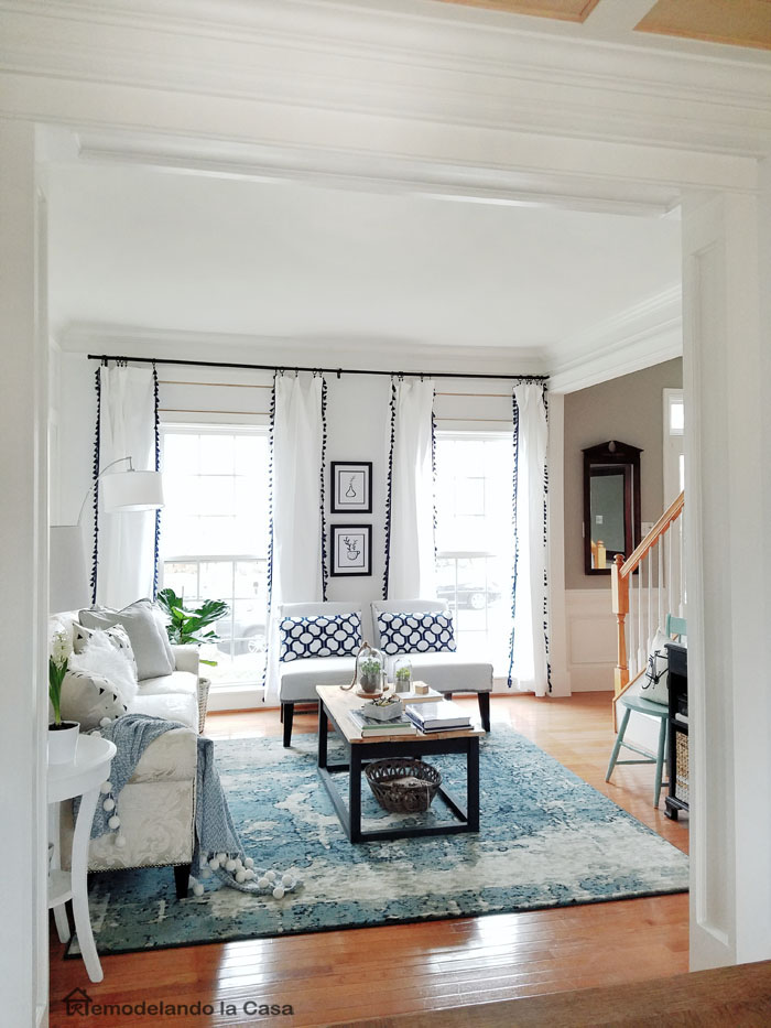 living room with blue rug and white curtains and industrial coffee table