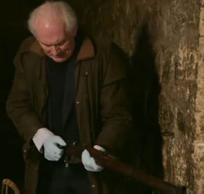 Screenshot of Dan Cruickshank holding a Lee Enfield rifle, similar to that which would have been used at the execution of Josef Jakobs on 15 August 1941. - Majesty & Mortar: Britain's Great Palaces - Opening the Palace Doors