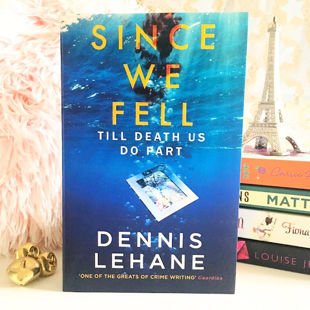 Since we fell by Dennis Lehane in the centre. Stack of books on the right side in the background with eiffel tower ornament on top, pink fluffy pillow on the left side