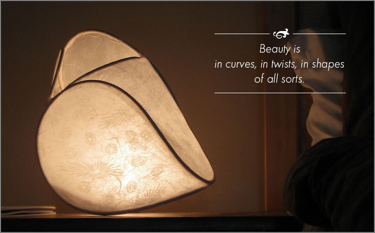 Light sculpture featuring floral impressions glows on bedside table.