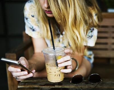 Chica utilizando una aplicación y tomando un smoothie