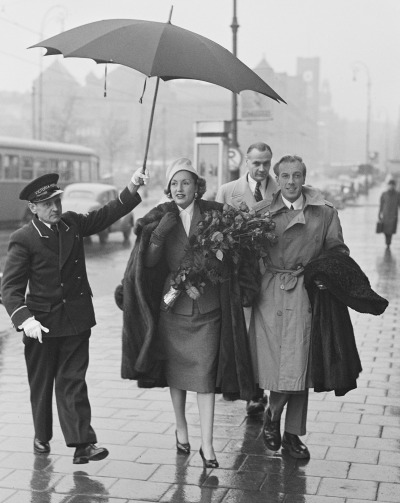Jacques Fath and wife Genevieve fashionably dressed and walking in the rain