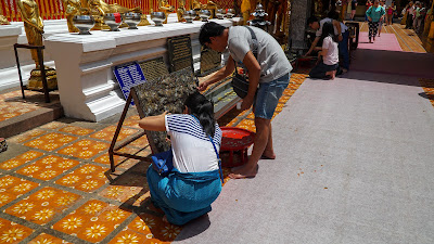 Visitors donating coins to the temple by trying to stick them onto a board