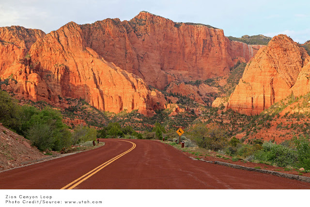 red road winding through tall red rocks