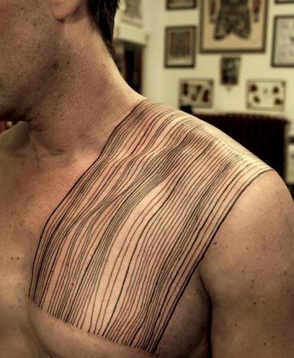 Preto ondulado linhas envoltório em torno do utente ombro, neste tatuagem reminiscência de uma folha.