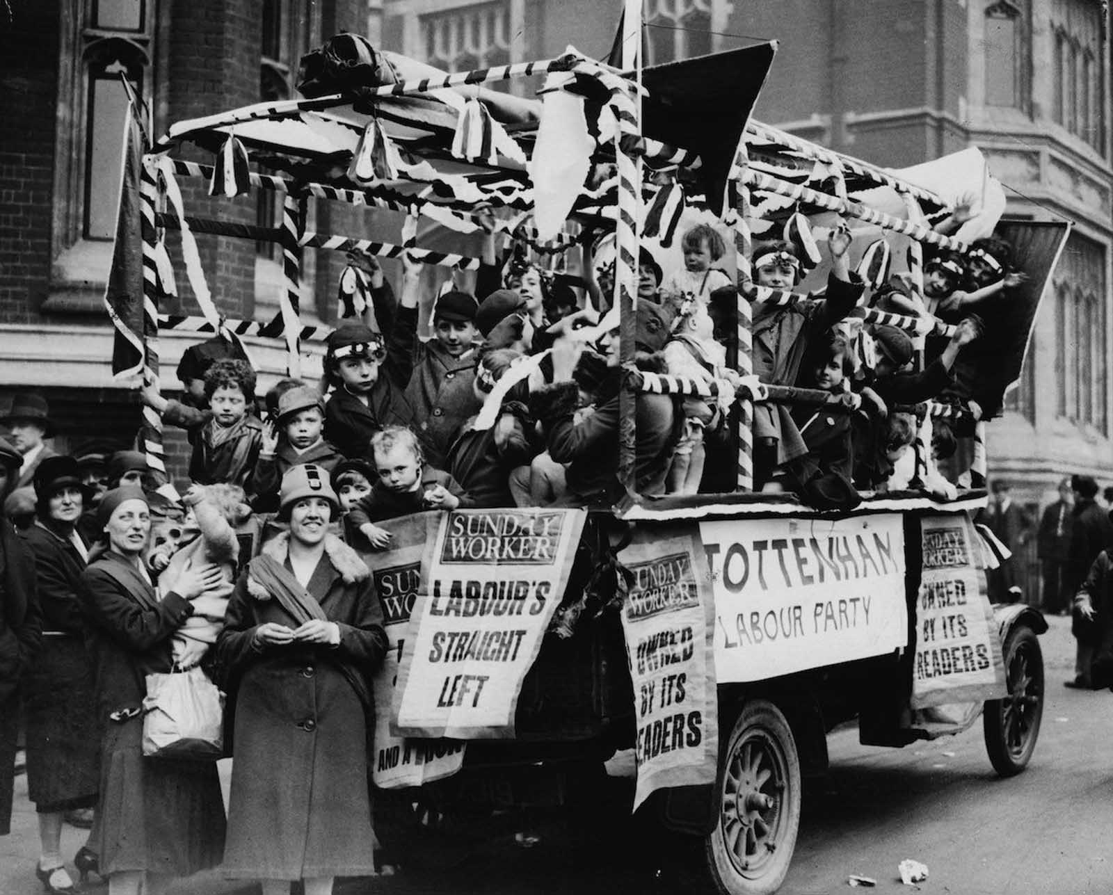 A Communist float covered with fliers from the Sunday Worker (the Sunday edition of the Daily Worker) and the Tottenham Labour Party, during a May Day parade and the Feast of Oratory in Hyde Park, London. 1928.