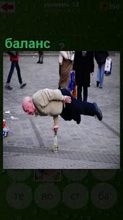мужчина на одной руке стоит на бутылке сохраняя баланс