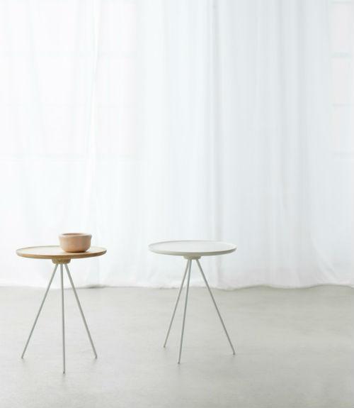 Tische mit drei Beinen stehen vor einer weißem Vorhang